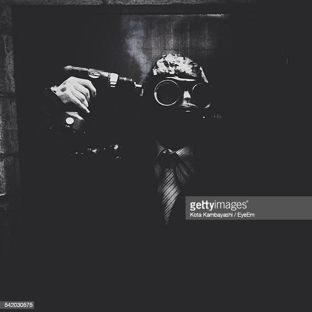 Businessman Wearing Gas Mask Holding Drill While Standing In Darkroom