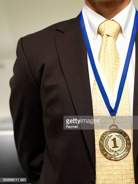Businessman wearing gold medal, close-up