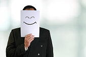 Business concept image of a businessman holding white paper mask with happy smiling face drawn on it