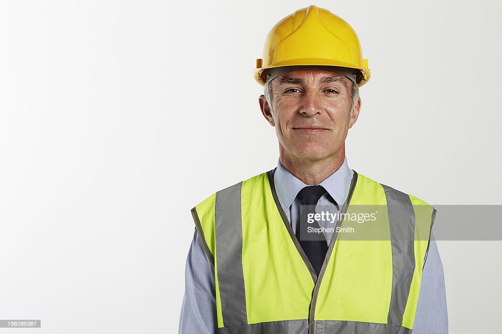 Businessman wearing hard hat and high vis jacket