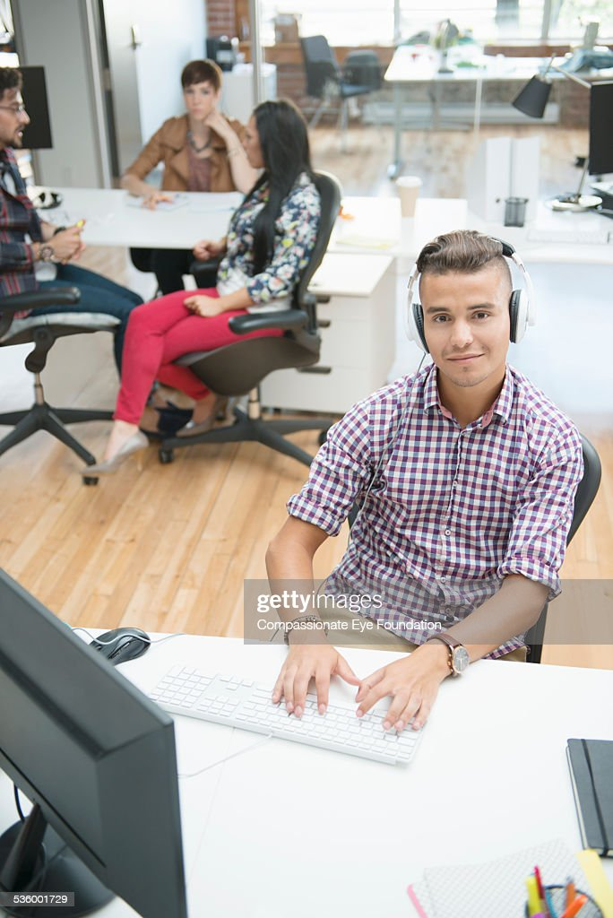 Businessman wearing headphones in office