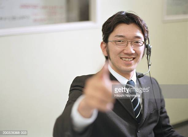 Businessman wearing headset and pointing, smiling