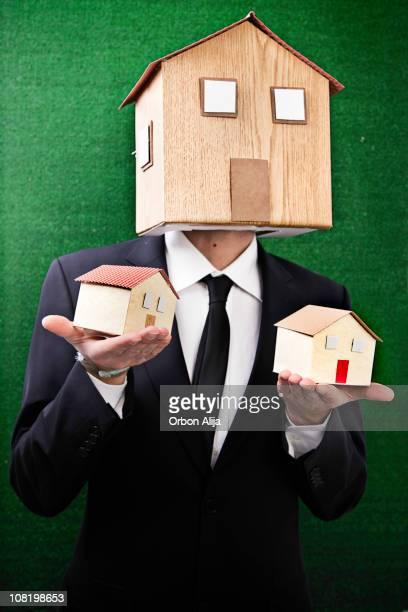 Geschäftsmann mit Hauses Maske, die zwei ähnlichen Häuser