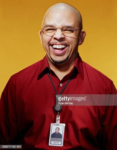 Businessman wearing ID badge around neck, portrait