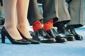 Businessman Wearing Individualistic Socks Between Two of His Colleagues
