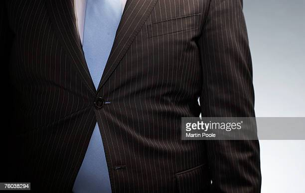 Businessman wearing jacket buttoned with only one button, mid section