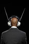 Businessman wearing large headphones, rear view