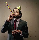 Businessman wearing party hat, blowing party blower, portrait
