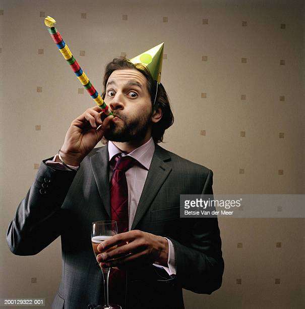 Businessman wearing party hat, blowing party blower, portrait