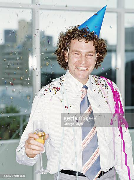 Businessman wearing party hat in office, holding champagne, smiling