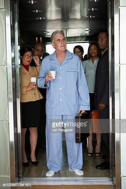 Businessman wearing pyjamas standing in elevator, colleagues smiling in background