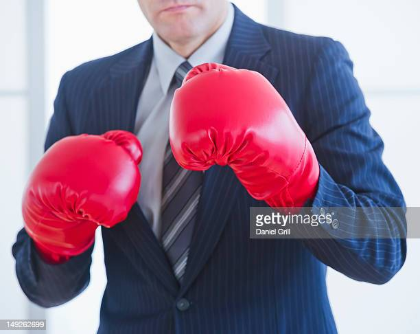 Businessman wearing red boxing gloves