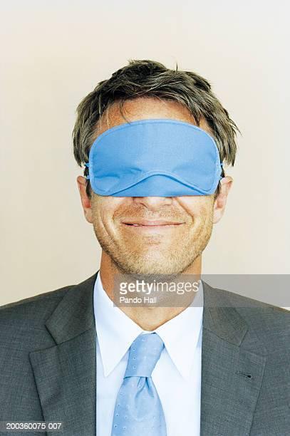 Businessman wearing sleeping mask, smiling, close-up