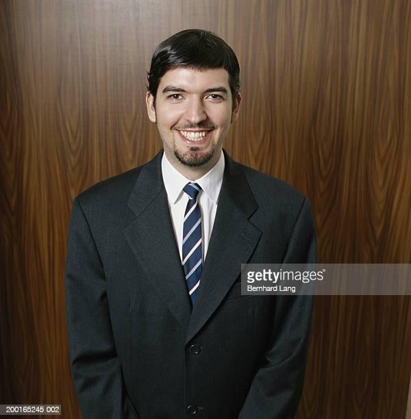 Businessman wearing smart suit, smiling, portrait
