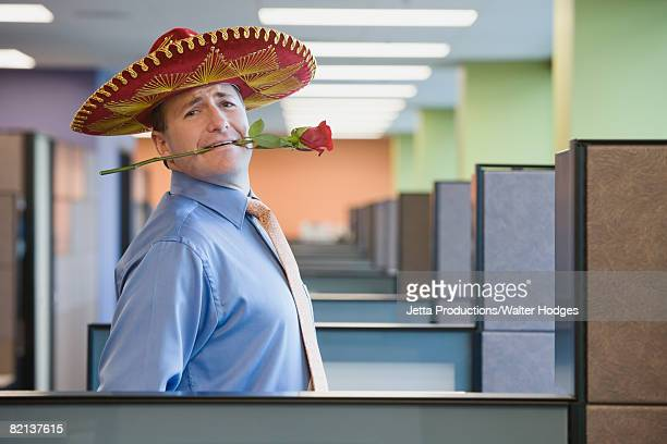 Businessman wearing sombrero and holding rose in teeth