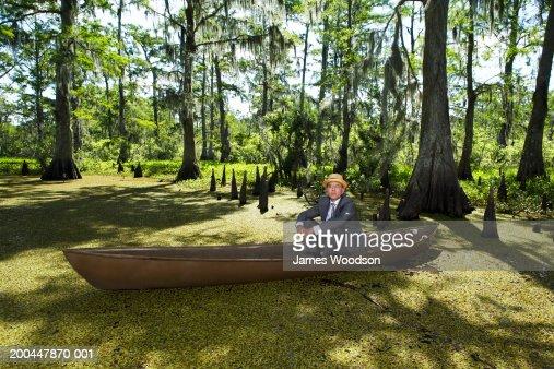 Businessman wearing straw hat sitting in boat in swamp, portrait