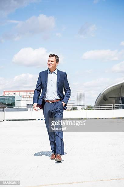 Businessman wearing suit walking on park deck, smiling