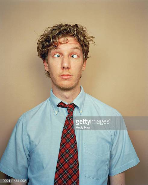 Businessman wearing tie making silly face