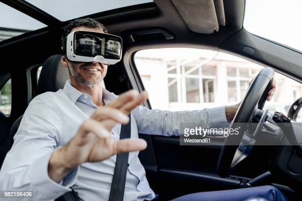 Businessman wearing VR glasses driving a car