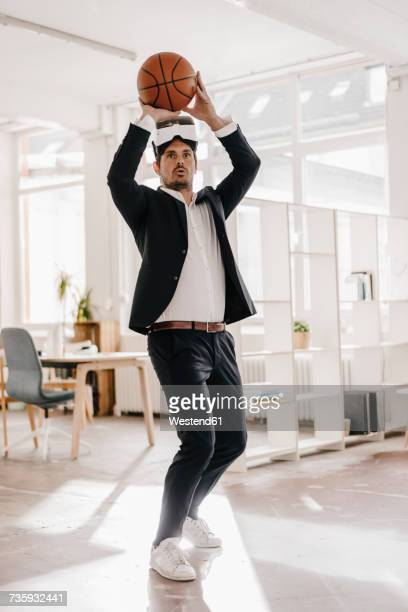 Businessman wearing VR glasses playing basketball in office