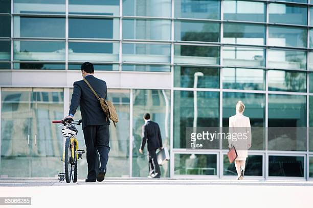 Businessman Wheeling Bicycle into Office Building