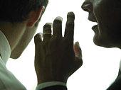 Businessman whispering another businessman, close-up