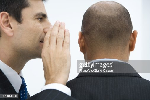 Businessman whispering in colleague's ear, close-up