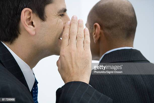 Businessman whispering to colleague