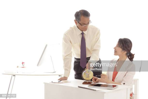businessman who consults while referring to the globe