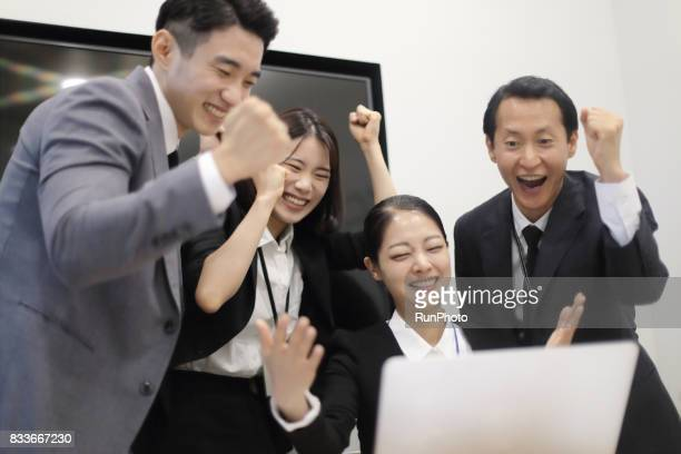 businessman who is happily cheering while watching a computer