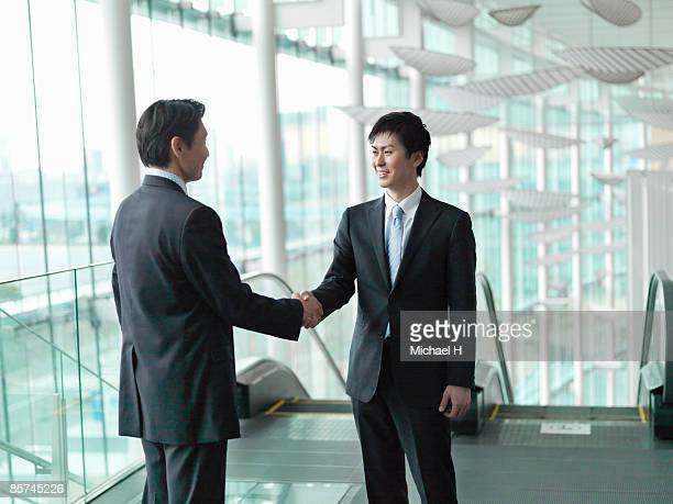 Businessman who shakes hands in escalator hall