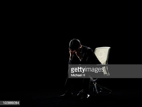 Businessman who sits on chair and worries : Stock Photo