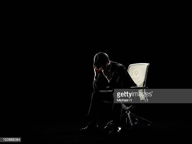 Businessman who sits on chair and worries