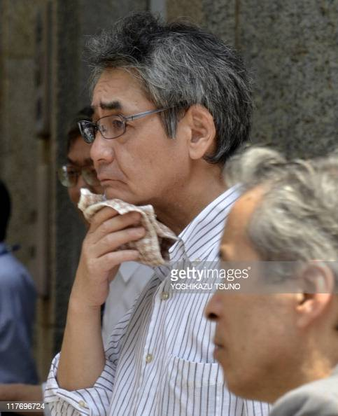 A businessman wipes his face in the heat along a street in Tokyo on June 30 2011 Air conditioners have been switched off office hallways are darkened...