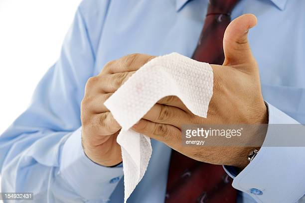 Businessman wiping hands with wet towel