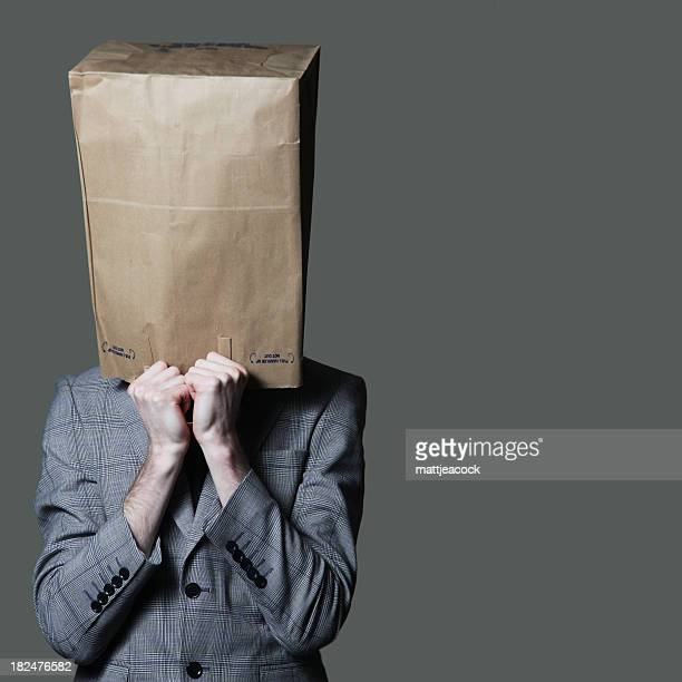 Businessman with a brown paper bag on his head