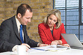Businessman with a businesswoman looking at documents in an office