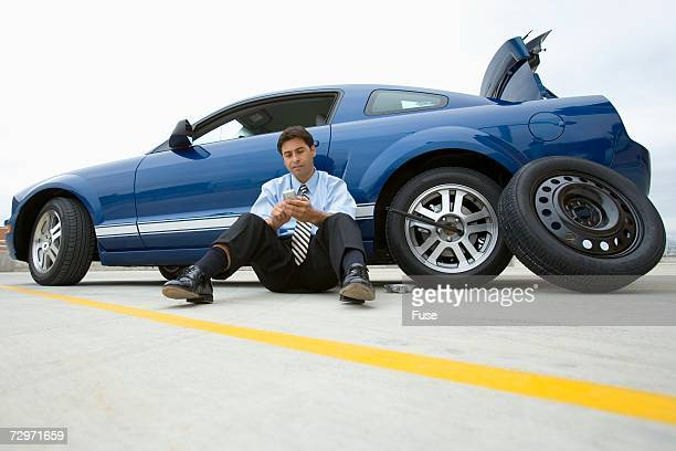 Businessman with a flat tire calling for help