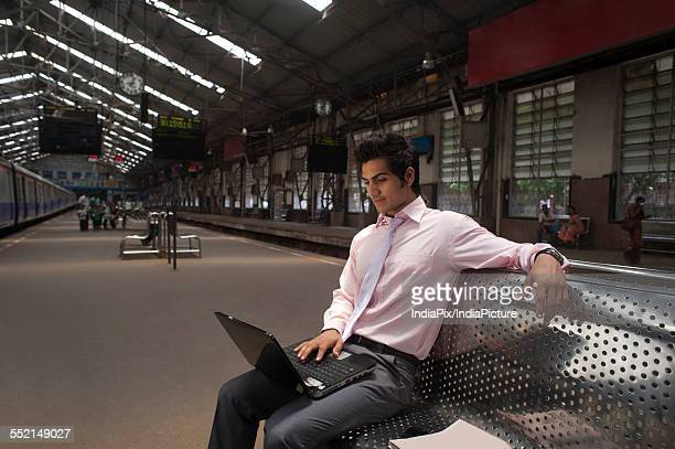 Businessman with a laptop at a train station