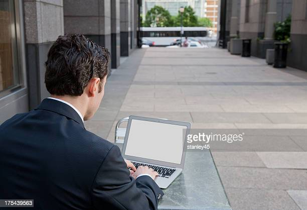 Businessman with a laptop in an outdoor public setting