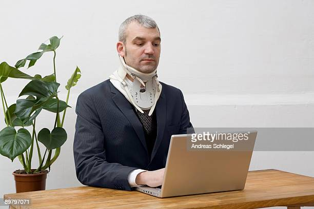 A businessman with a neck brace working on a laptop