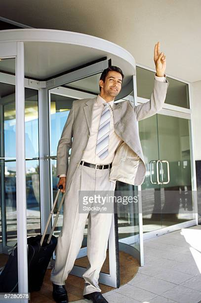 Businessman with a suitcase hailing a taxi