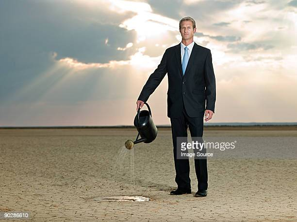 Businessman with a watering can in the desert