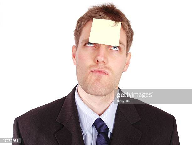 A businessman with a yellow sticky note on his forehead