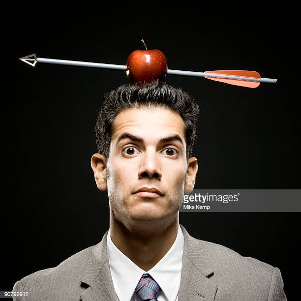 businessman with an apple on his head that has been shot with an arrow