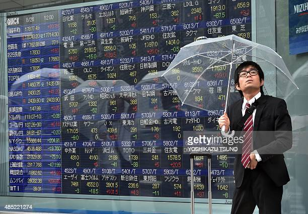 A businessman with an umbrella looks up to the rainy sky as he passes a share prices board in Tokyo on August 26 2015 Tokyo shares rebounded at the...