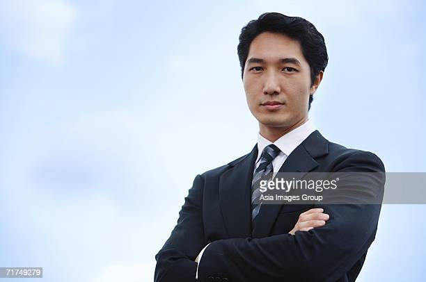 Businessman with arms crossed, looking at camera