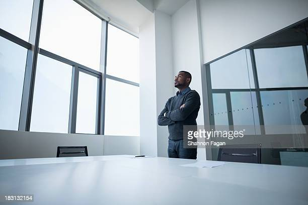 Businessman with arms crossed looking out
