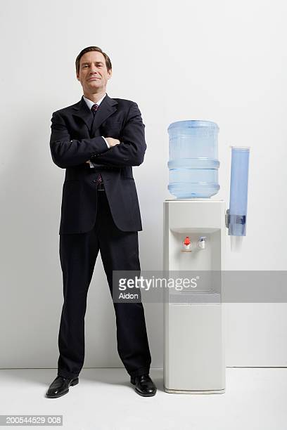 Businessman with arms crossed, standing by water cooler, portrait