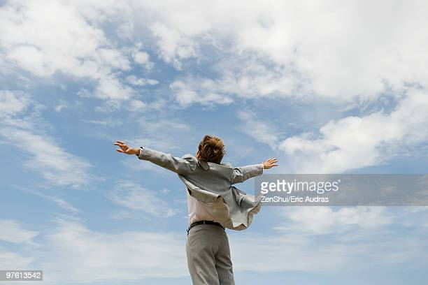 Businessman with arms outstretched against cloudy sky, rear view